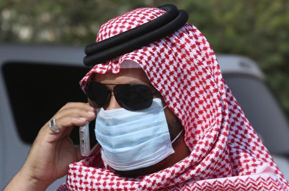 Man with mask speaks on his mobile phone in Jeddah