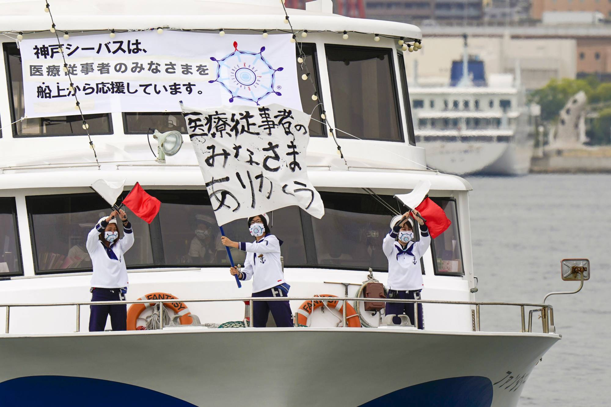Crew members of a sightseeing boat signal 'thank you' off Kobe Port on May 15 to express their appreciation to medical workers battling the COVID-19 outbreak. | KYODO